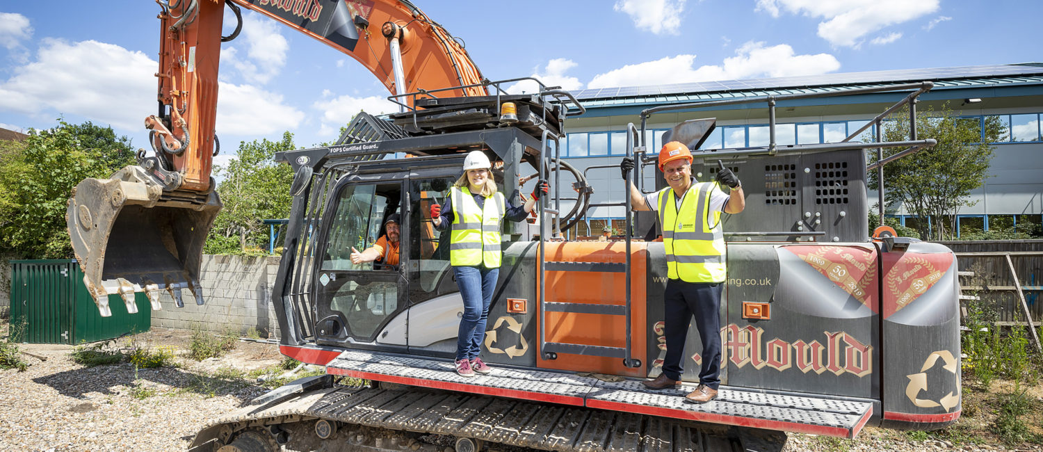 Two borough councillors standing on a large digger