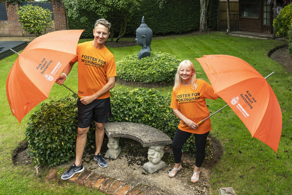 Ian Waite and foster carer Sue Rayment in a garden holding umbrellas