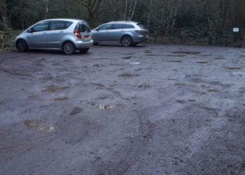 car park with rough surface and puddles with two cars parked