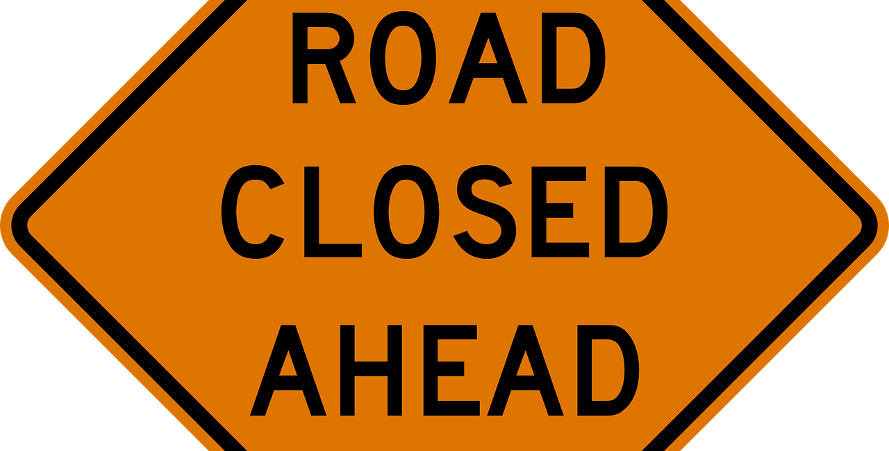 orange and black road closed ahead sign