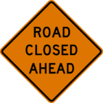 orange and black road closed ahead sign