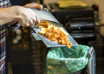 Vegetable peeling being scraped into a food waste caddy