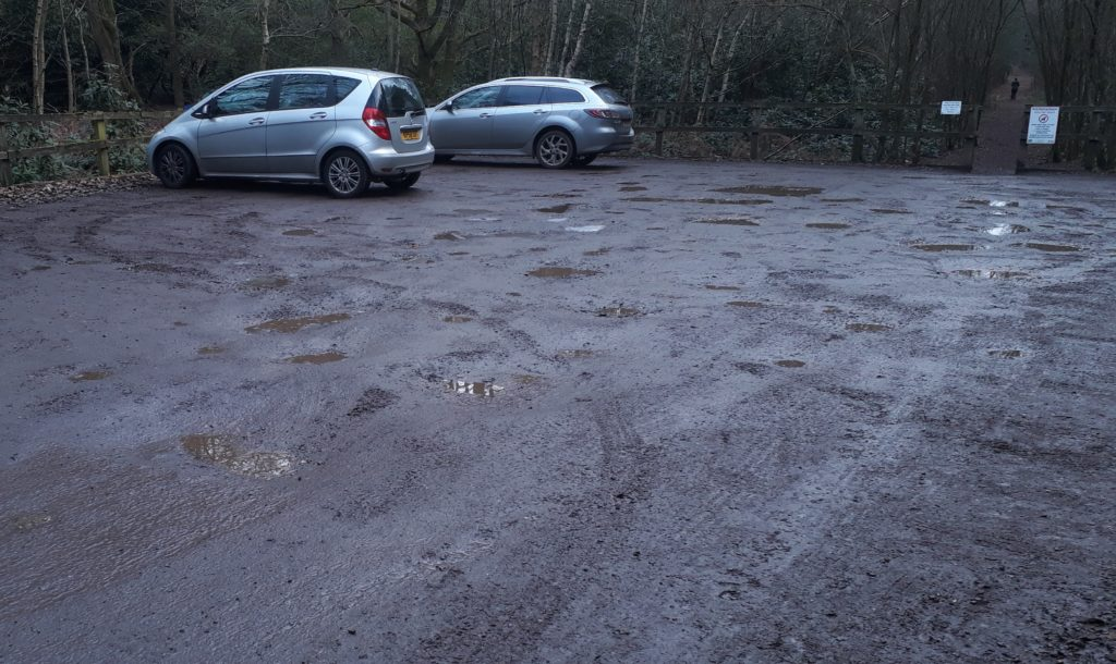 car park surface with pot holes and puddles