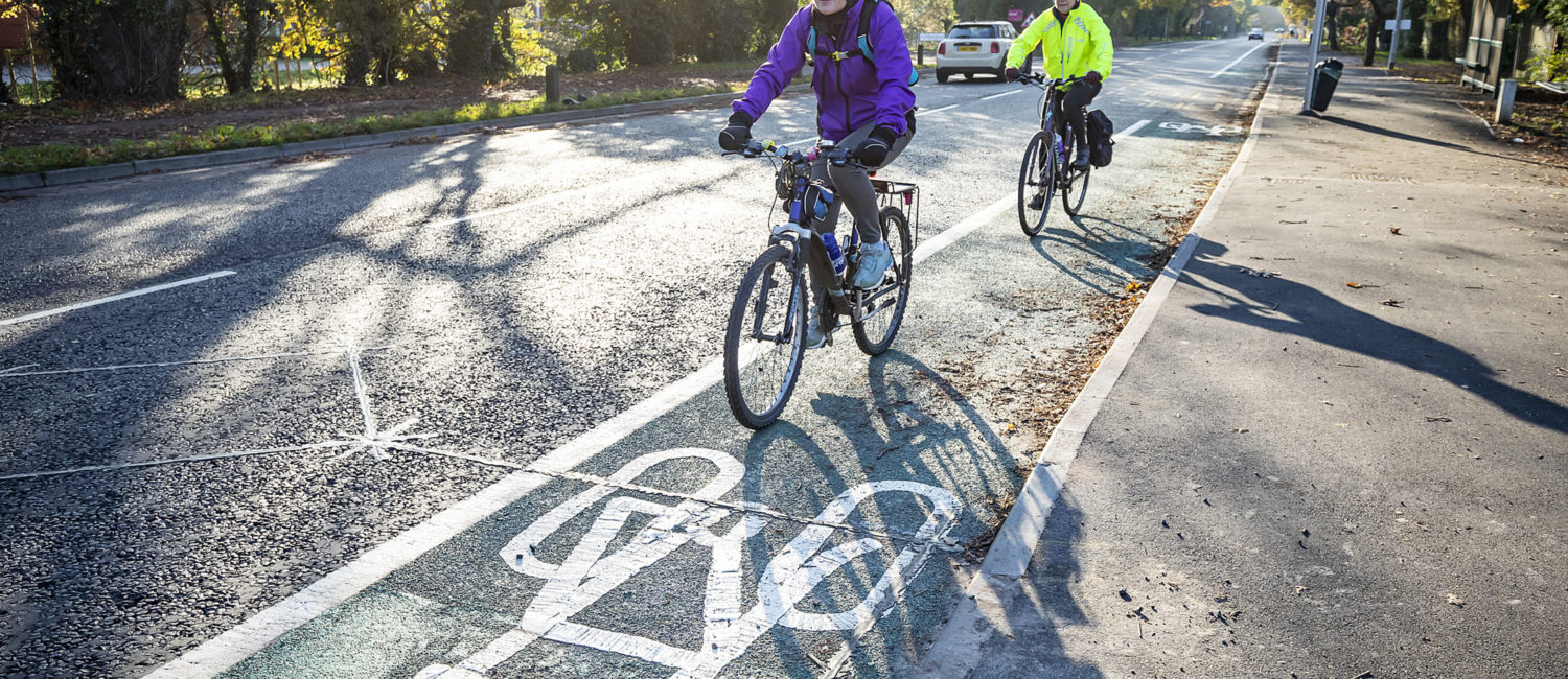 two cyclists on a cycle lane alongside a roadway